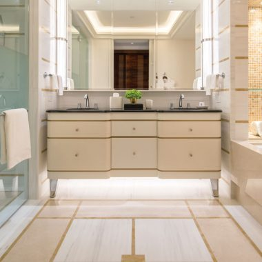 A granite vanity separates a soaking tub and shower in the bathroom of this suite